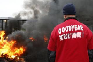 File picture of an employee of US tyre-maker Goodyear standing in front of burning tires at the entrance of the plant in Amiens, northern France